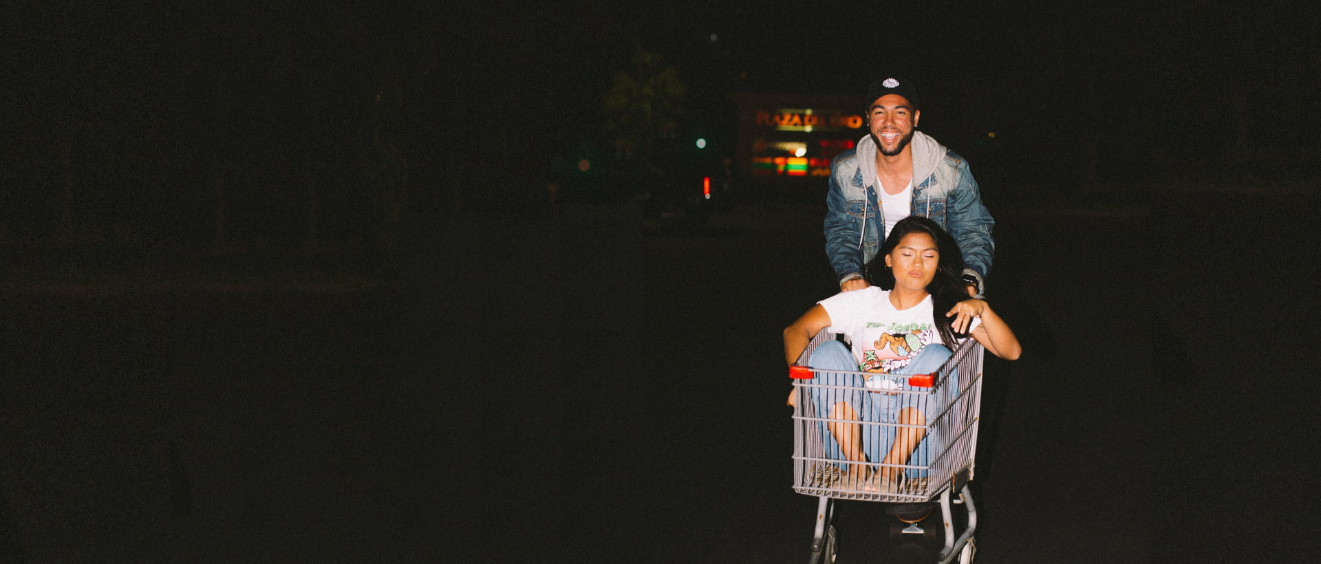 With us eCommerce is fun and easy like for a happy couple with a girl in a shopping cart